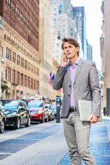 Young Businessman traveling, working in New York, wearing gray blazer, patterned shirt, holding laptop computer, standing on street in Manhattan, talking on cell phone, looking up, frowned, worried..