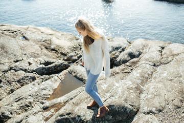 Cute female teen on rocks on ocean