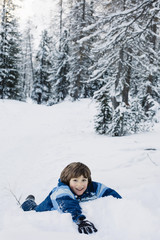Little boy laying in the snow and smiling while looking at camera