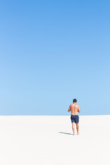 Back view of young man on the beach with blue sky and copyspace