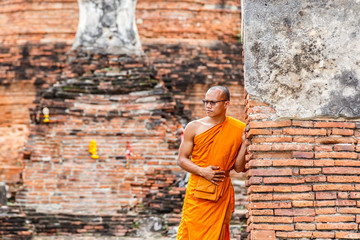 Monk standing and look at view in front of buddha statue at old temple, Ayutthaya Province, Thailand