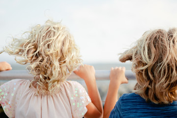 two kids hold on to the railing of a ferry while the wind whips through their hair