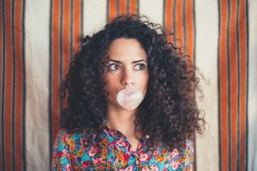 Girl with curly hair blowing a bubble with a pink bubble gum