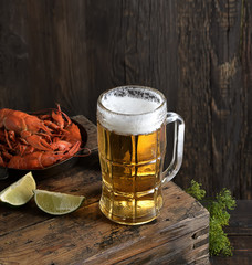 Glass of beer and a boiled crayfishes in a plate on a wooden background