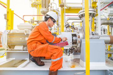 Mechanical technician checking and logging data and lube oil lubrication system of electric motor and centrifugal pump which is his daily activity at offshore oil and gas central processing platform.