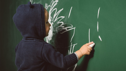 Child drawing with chalk on the blackboard
