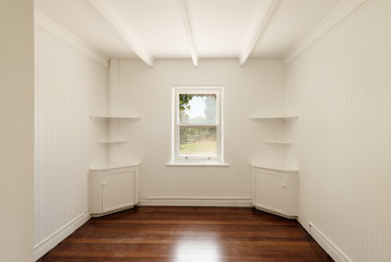 empty room with freshly painted white walls and polished timber floors