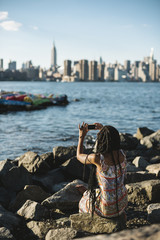 Young black woman relaxing against New York skyline