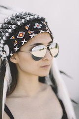 young woman in a  headdress ,selective focus on sunglasses .