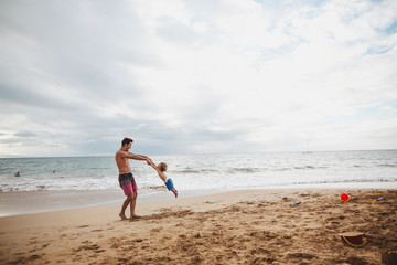 Young dad swinging his son around on tropical beach