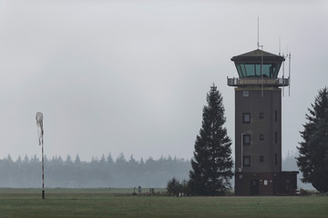 Old air traffic tower in meadow with pine trees.
