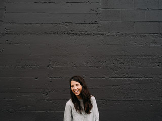 Stylish girl in front of black wall