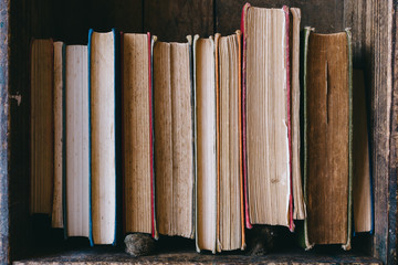 Close up of old hardcover books in a wooden books