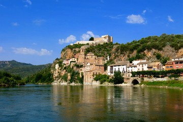 Miravet, Catalonia, Spain on Ebro River. Medieval castle once occupied by the Knights Templar towers over village.
