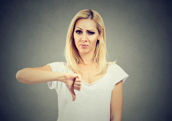 Woman giving thumb down gesture looking with negative expression and disapproval