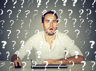Perplexed man working on desktop computer has many questions