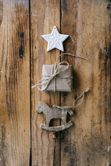 Small paper wrapped Christmas gift with wooden horse and star ornaments - vertical