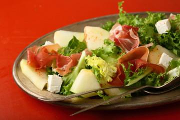 Fresh salad with prosciutto and melon slice