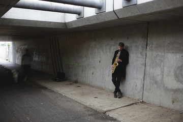 Saxophone player in urban tunnel