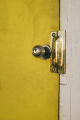 Close up door knob and brightly colored yellow door on building exterior