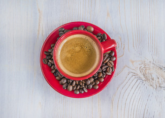 red cup of coffee on light wooden background top view