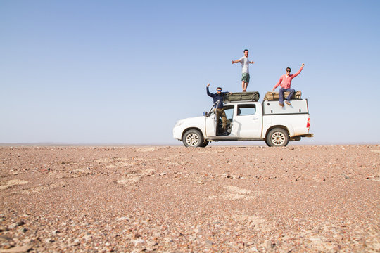 Group of happy friends on top of an off-road vehicle in the middle of the desert - Adventure travel