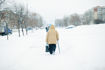 An elderly woman with cane is walking along a snow-covered pavement. Heavy snowfall in the city.