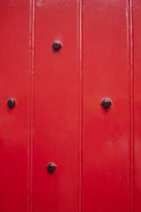 puerta de madera de color rojo con clavos en metal negro