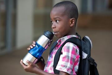 little boy drinking water in a bottle.