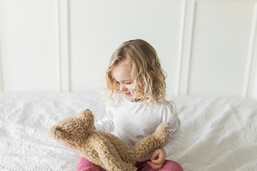 Young girl wearing red and white striped pajamas looks at teddy bear