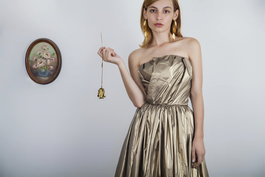 Young beautiful woman with freckles and brown hair in a golden dress