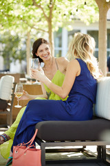 Woman Holding Wineglass While Looking At Friend At Outdoor Restaurant