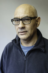 Portrait of a bald man with glasses on.
