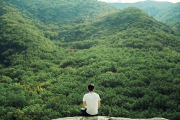 Retrato de hombre joven de espaldas frente a un frondoso verde bosque en la colina de una montaña. El retratado se sitúa en una gran roca observando toda la naturaleza frente a él.