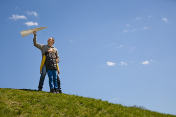 Portrait of man and kid boy sitting on top of hill and going to start paper airplane. Father and son together.
