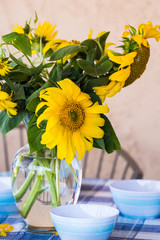 Blue, outdoor table setting with yellow sunflowers and blue checkered tablecloth
