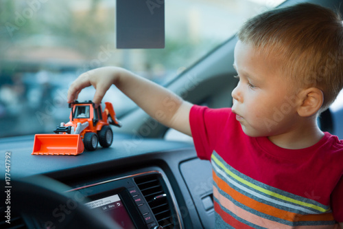 ff7655c14 Portrait of cute toddler boy sitting in a car and playing with his plastic  tractor. Child holding his toy while being in a car.