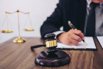 Gavel on wooden table and Lawyer or Judge working with agreement in Courtroom theme, Justice and Law concept