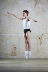 Little ballet caucasian boy dancing in a studio in white shirt and black underpants ballet uniform. Full-length portrait.