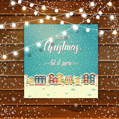 """Christmas wooden background with greeting card with houses and hand made quote """"Merry Christmas.let it snow"""". Winter town. New Year. Festive poster. Lettering. Banner, poster, flyer, brochure."""