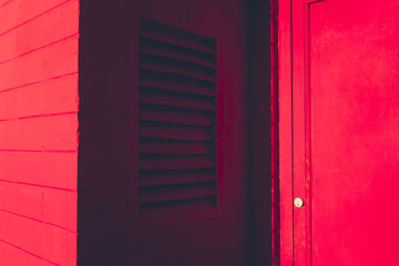 Exterior of red colored wall, vent and door lock