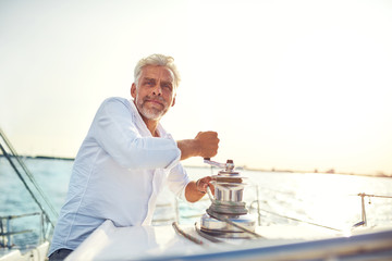 Mature man using winch on his boat while out sailing