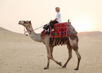 blonde Frau reitet auf einem Kamel durch die Wüste vor orangem Himmel