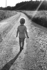 Small child walks barefoot on an open road.