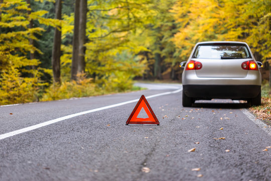 Red triangle of a car on the road.Broken car in forest.damage car with reflective triangle