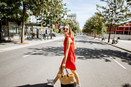 Lifestyle portrait of a woman in red dress crossing the street at the modern district of Barcelona city