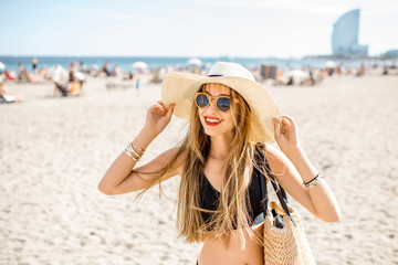 Lifestyle portrait of a pretty woman with sunhat and bag on the beach in Barcelona