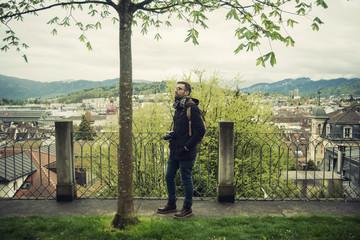 Retrato de turista en un parque de Lucerna, Suiza. Observando un árbol y la naturaleza a su alrededor y con la ciudad de fondo.