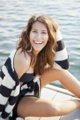 Young female sitting on a dock wearing bikini smiling to camera
