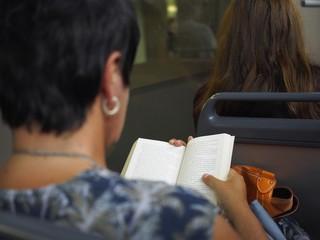 Frau liest ein Buch in der Straßenbahn